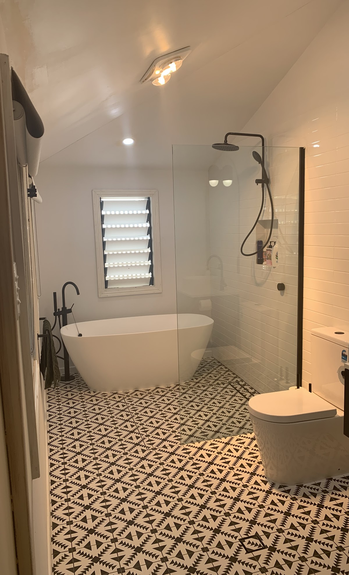white marble bathroom with a toilet and shower that has mosaic floor tiles
