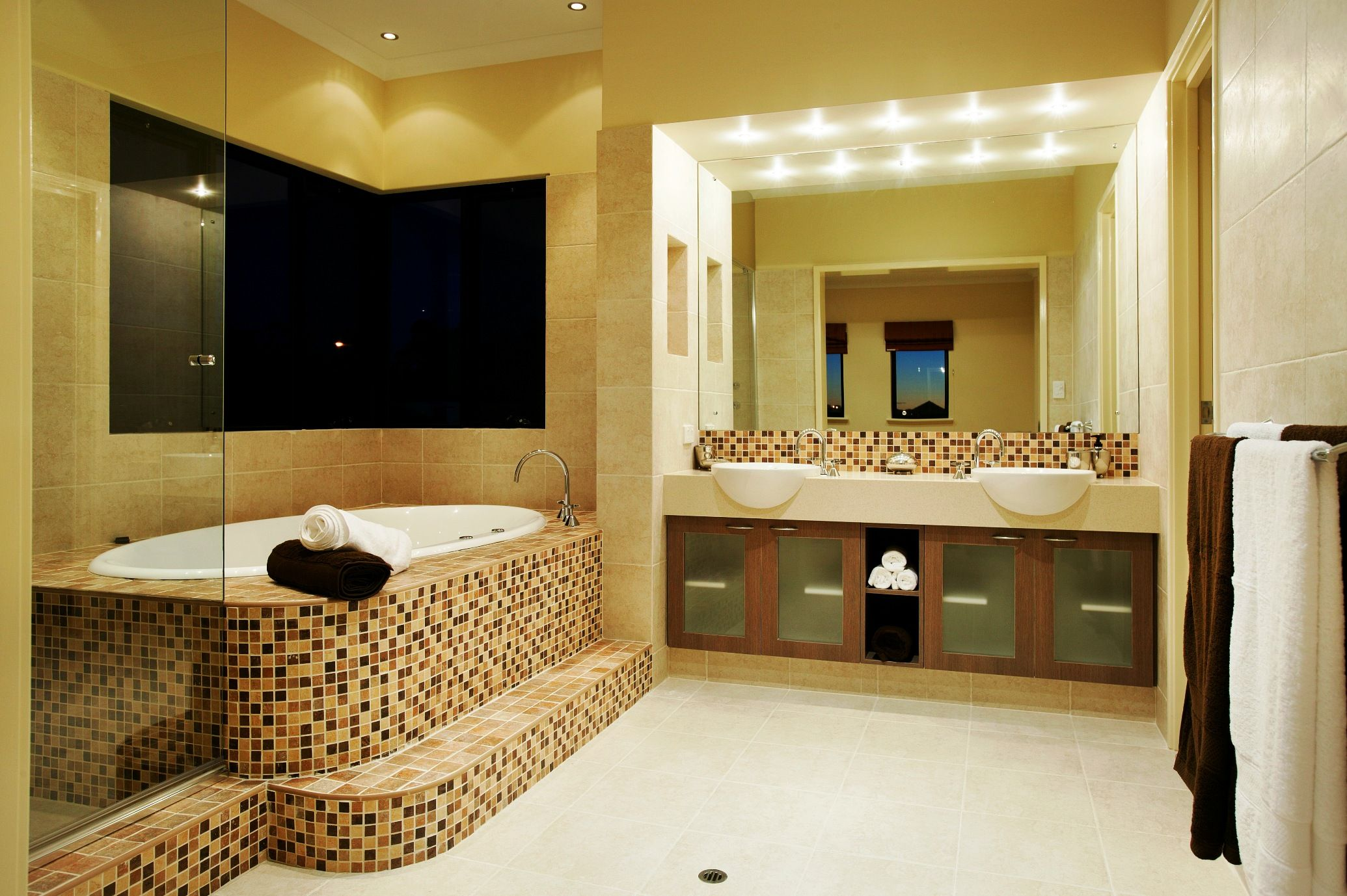 yellow marble bathroom with a white marble floor, a mirror and a spa with mosiac tiling